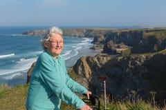 活跃愉快的年长女性领抚恤金者与流动性框架和拐棍的80由美好的海岸场面 免版税图库摄影