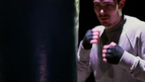 活跃拳击袋子的一个年轻人 库存图片