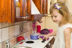 活跃矮小的学龄前年龄孩子,有白肤金发的卷发的逗人喜爱的小孩女孩,显示演奏厨房,由木头制成,戏剧 免版税图库摄影