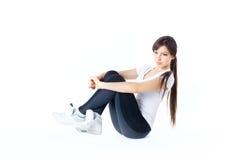 活跃穿戴的妇女坐地板 库存照片