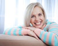 活跃美好中年妇女微笑友好和调查照相机 妇女的接近的表面s 免版税库存图片