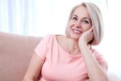 活跃美好中年妇女微笑友好和调查照相机 妇女的接近的表面s 库存图片