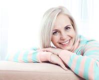 活跃美好中年妇女微笑友好和调查照相机 库存图片