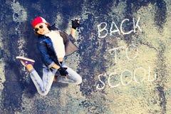 跃迁的女孩少年 牛仔布衣物 棒球帽 以老混凝土墙为背景 回到Scho的题字 免版税库存照片