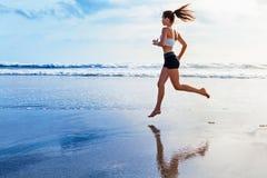活跃运动的妇女沿日落海洋海滩跑 炫耀背景 免版税库存照片