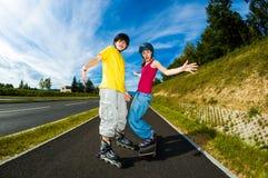 活跃青年人- rollerblading,踩滑板 图库摄影
