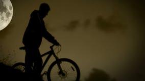 活跃骑自行车的人跑与在夜月光的自行车 影视素材