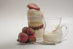 跌倒入飞溅的新鲜的草莓牛奶在点心附近 免版税图库摄影