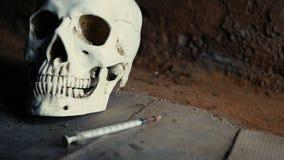 跌倒喷洒的血液在海洛因可卡因射入以后的注射器以头骨为背景 影视素材