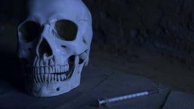 跌倒喷洒的血液在海洛因可卡因射入以后的注射器以头骨为背景 股票视频