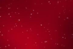 跌倒圣诞节的雪花流动从在红色梯度背景,寒假xmas的上面的雪 库存图片