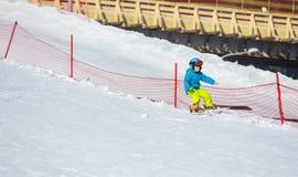 跌倒的小男孩,当滑雪对于儿童区域时 免版税库存照片