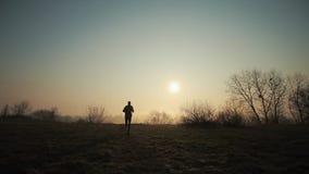 跑一个的人的剪影在阳光下 日出或日落在背景 股票录像
