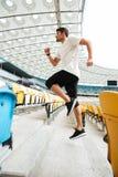 跑一个运动的运动员的人的侧视图在楼上 图库摄影