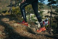 跑上升在山行迹的公赛跑者的特写镜头脚 免版税库存图片