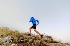 跑上升在石头男性运动员 图库摄影