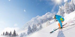 跑下坡在美好的高山风景的滑雪道的滑雪者 在背景的蓝天 库存图片