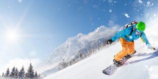 跑下坡在美好的高山风景的滑雪道的滑雪者 在背景的蓝天 免版税库存照片