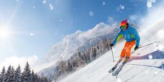 跑下坡在美好的高山风景的滑雪道的滑雪者 在背景的蓝天 免版税库存图片