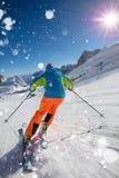 跑下坡在美好的高山风景的滑雪道的滑雪者 在背景的蓝天 免版税图库摄影