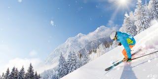 跑下坡在美好的高山风景的滑雪道的滑雪者 在背景的蓝天 图库摄影