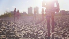 跑与一个球的英俊的运动人在他的手上到他的朋友,打沙滩排球 股票录像