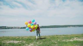 跑与五颜六色的气球到湖湖的愉快的女孩 4K 影视素材