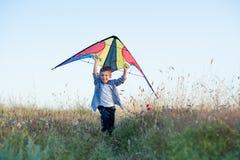 跑与五颜六色的风筝的愉快的英俊的小男孩在他的手上在头顶上 免版税库存照片