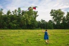 跑与五颜六色的风筝的Irl 库存图片