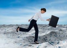 跑与公文包的女实业家在文件海在蓝天下覆盖 库存照片