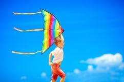 跑与在天空背景的风筝的愉快的年轻男孩 免版税库存图片
