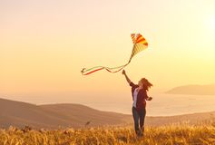 跑与在沼地的风筝的愉快的少妇在日落在夏天 免版税图库摄影