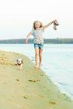 跑与在海滩的一条狗的女孩 库存照片