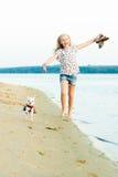 跑与在海滩的一条狗的女孩 免版税库存图片