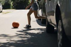 跑与在行人交叉路的球的女孩 免版税库存照片