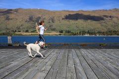 跑与她的狗的年轻妇女 免版税库存照片