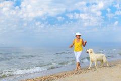 跑与她的golder猎犬的年长妇女 库存图片