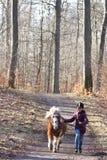 跑与小马的女孩 免版税库存照片