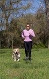 跑与您的狗的女孩 免版税库存图片