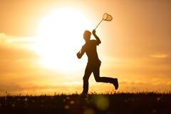 跑与昆虫网的年轻人在日落 库存图片