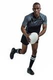 跑与橄榄球球的坚定的运动员画象 免版税库存照片