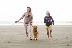 跑与狗的妇女和孩子 免版税库存照片