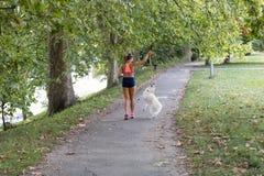 跑与狗的年轻可爱的体育女孩在公园 免版税库存照片