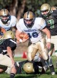 跑与球的美国橄榄球运动员在比赛期间 免版税图库摄影
