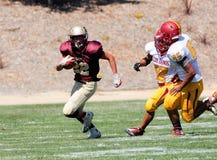 跑与球的美国橄榄球运动员 免版税库存照片