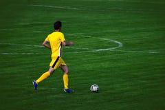 跑与球足球运动员 免版税图库摄影