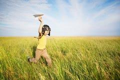 跑与纸飞机的年轻男孩 免版税库存图片