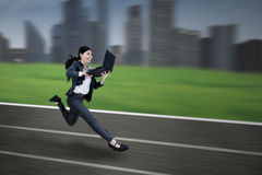 跑与膝上型计算机的亚裔女实业家 库存照片