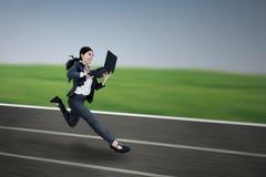 跑与膝上型计算机的可爱的女实业家 免版税库存图片