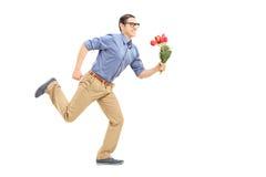 跑与花的人在他的手上 免版税库存图片